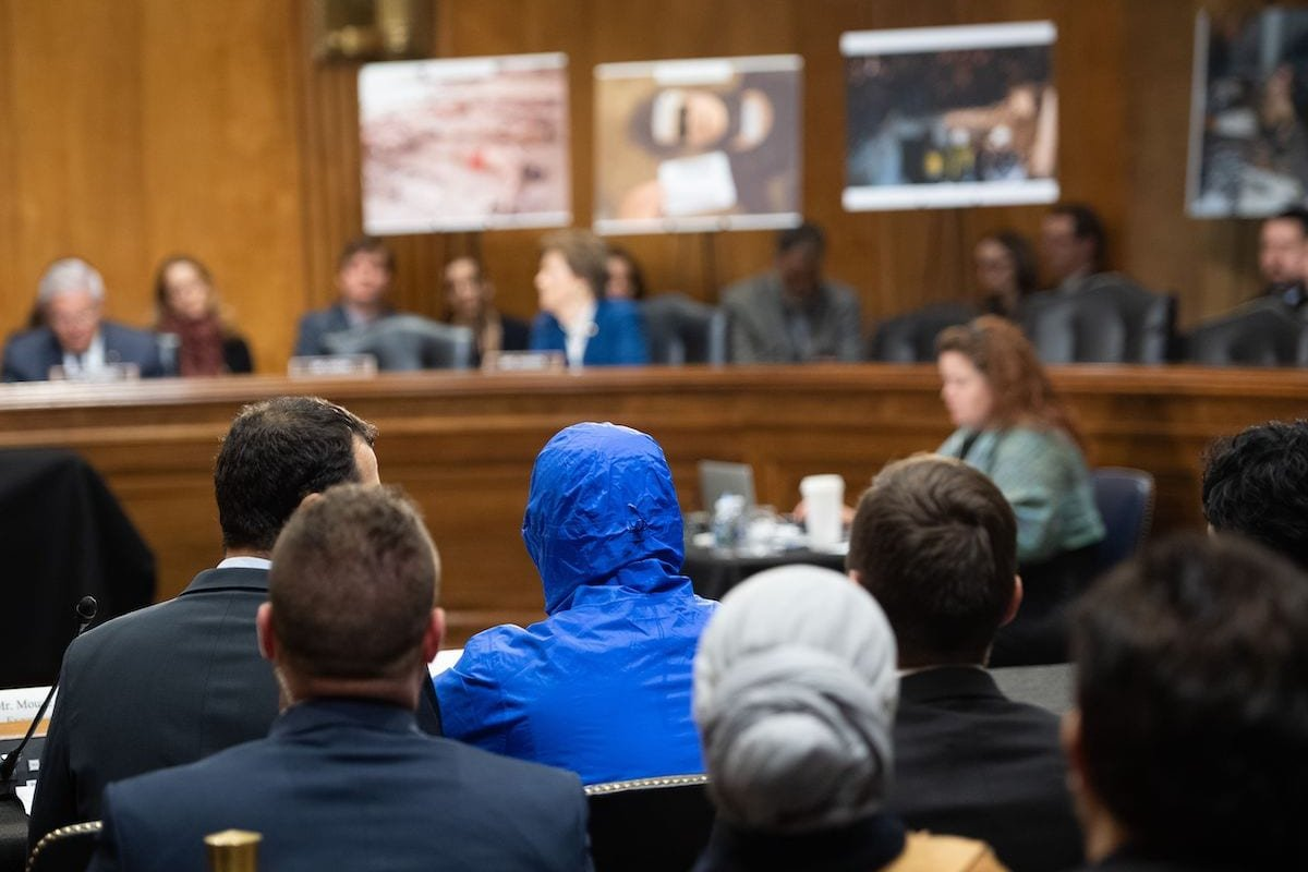A Syrian military defector using the pseudonym Caesar, while also wearing a hood to protect his identity, testifies about the war in Syria during a Senate Foreign Relations committee hearing on Capitol Hill in Washington, DC, 11 March 2020. [SAUL LOEB/AFP via Getty Images]