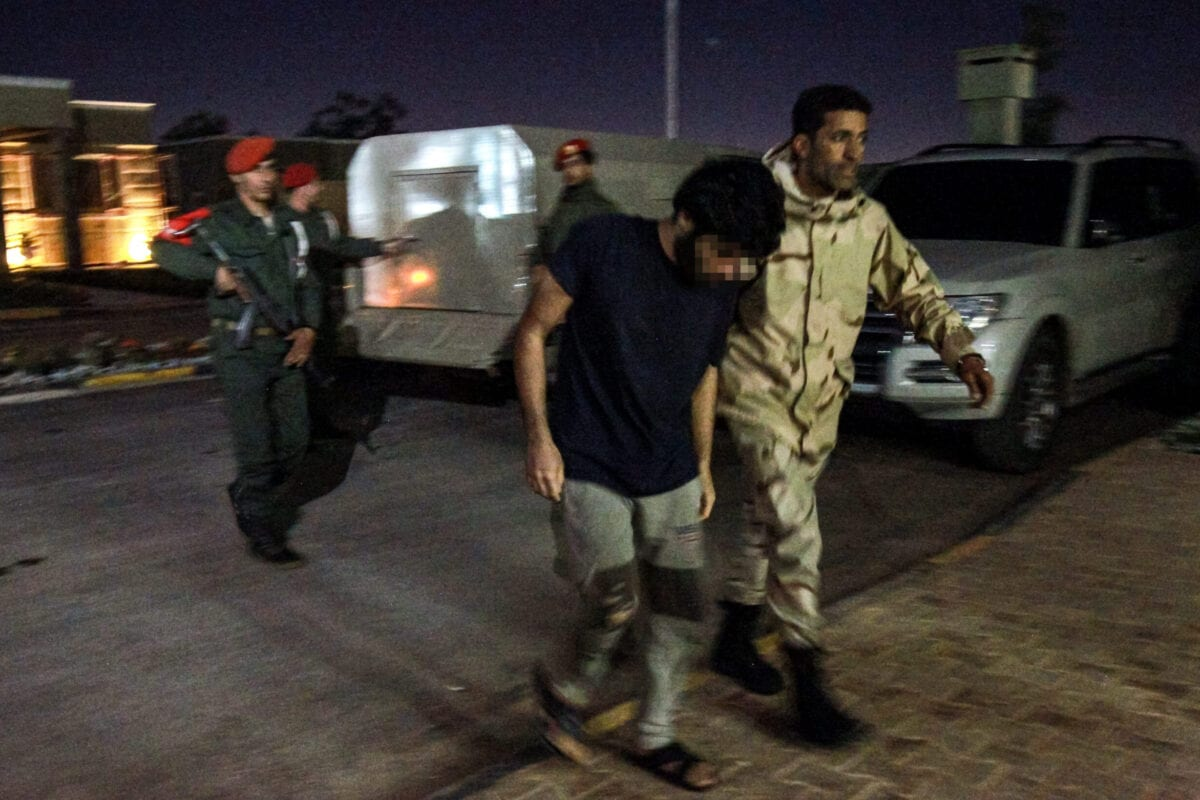 This picture taken on May 5, 2020 in Libya's eastern city of Benghazi, currently controlled by forces loyal to strongman Khalifa Haftar, shows a pro-Haftar soldier escorting a prisoner captured by Haftar's forces reportedly during their offensive near Tripoli, alleged to be part of mercenaries from Syria brought over by Turkey. [ABDULLAH DOMA/AFP via Getty Images]