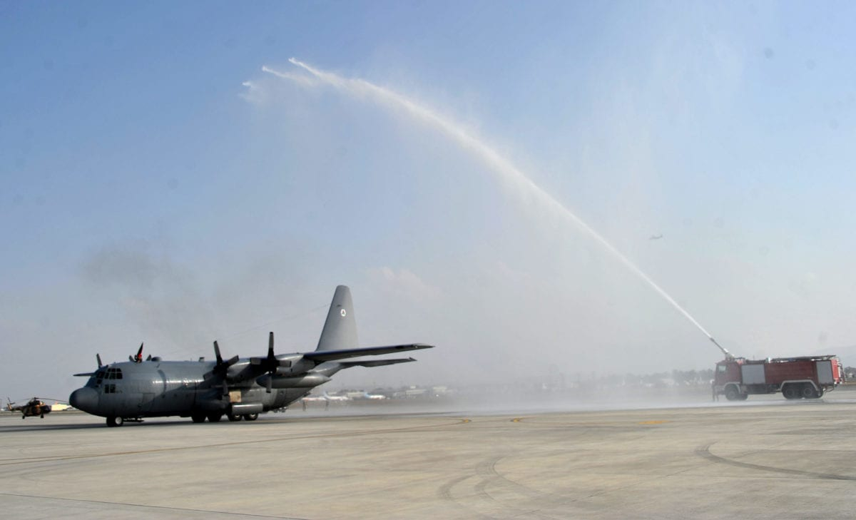 A water jet is sprayed over a C-130 transport aircraft on its arrival at Kabul international airport on October 9, 2013. [Noorullah Shirzada/AFP via Getty Images]