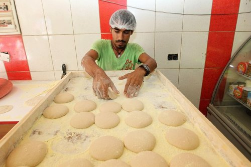 Lebanese baker arranging bread loafs at a bakery in the Lebanese capital, Beirut [ANWAR AMRO/AFP via Getty Images]