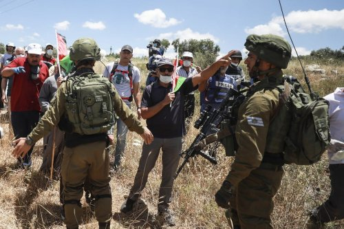 Israeli security forces stop a protest against the construction of illegal settlements in the West Bank on 29 May 2020 [Issam Rimawi/Anadolu Agency]