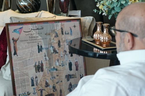 The Palestinian Mahmoud is looking to a map of his home, Palestine [Eman Abusidu- Middle East Monitor]