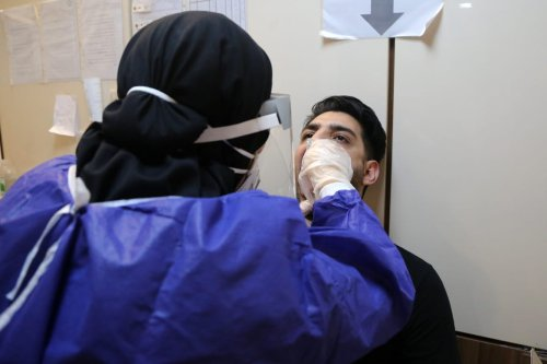 An official of Keyvan Virology Laboratory takes a sample from a man as people arrive to have Covid-19 test due to rises in coronavirus cases in Tehran, Iran on July 14, 2020. [Fatemeh Bahrami - Anadolu Agency]