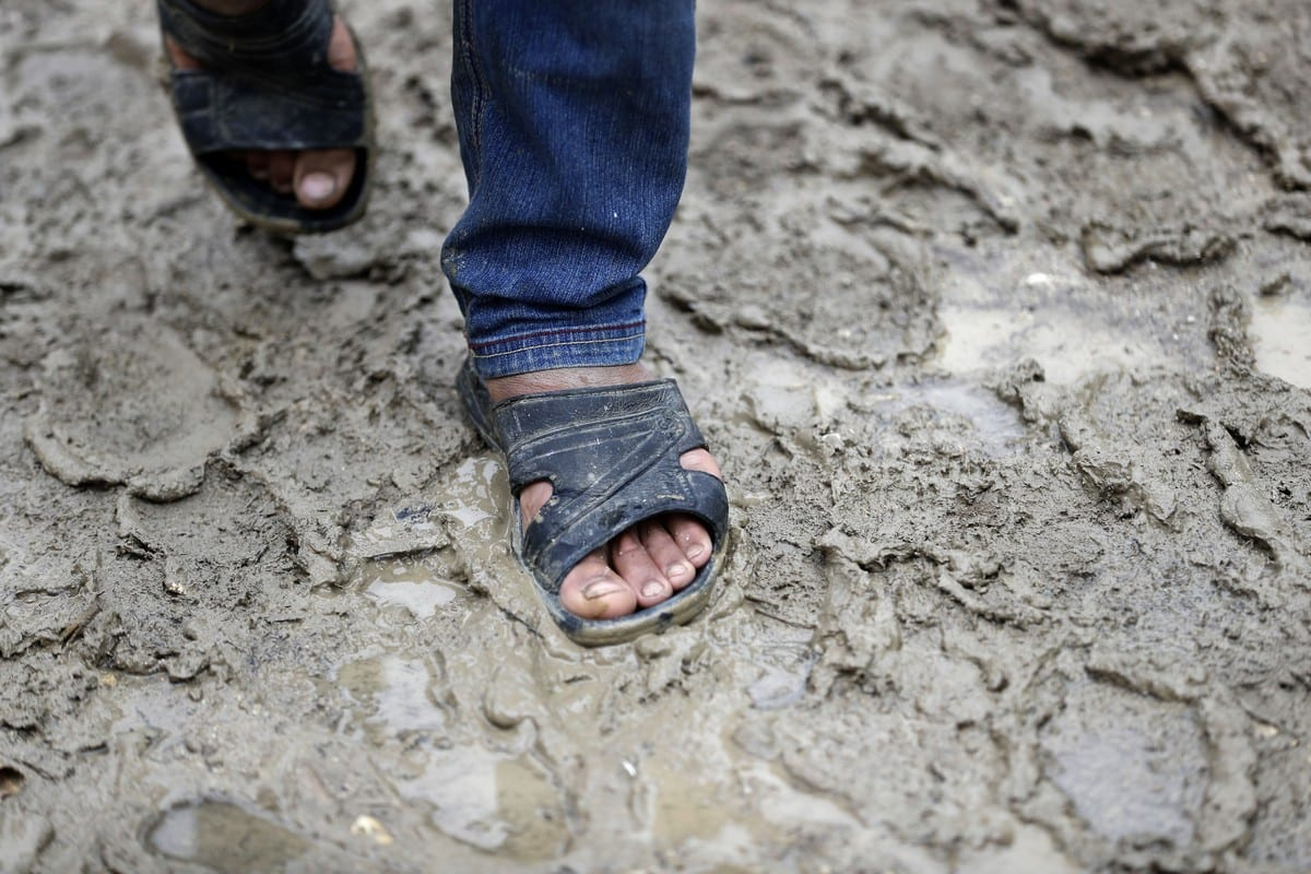 A Syrian boy walks through the mud down an alley at a refugee camp in Lebanon, 10 July 2020 [JOSEPH EID/AFP/Getty Images]