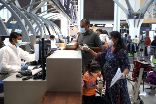 Indian nationals check in at the Muscat International Airport, in Muscat, Oman on May 9, 2020 [MOHAMMED MAHJOUB/AFP via Getty Images]