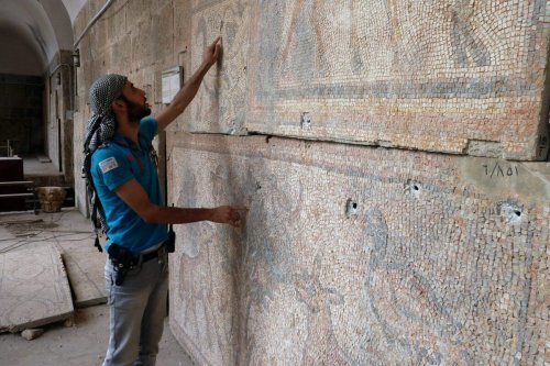 A Syrian rebel fighter inspects a mosaic at the Alma Arra museum in Maarat al-Numan, in Syria's northwestern Idlib province, on October 11, 2012 [HERVE BAR/AFP/GettyImages]