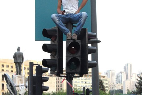 A supporter of the March 14th anti-Syrian opposition coalition, sits watching from on top of a set of traffic lights , on October 21, 2012 [ANWAR AMRO/AFP via Getty Images]