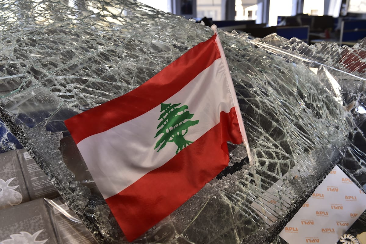 A Lebanese flag is seen in the rubble after the explosion in Beirut, Lebanon on 5 August 2020 [Houssam Shbaro/Anadolu Agency]