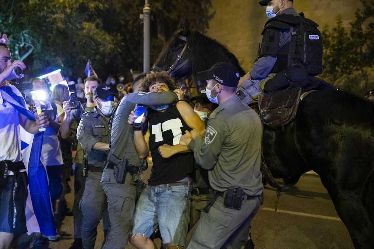 Israeli police officers take a protester into custody as thousands of people stage a protest against Israeli Prime Minister Benjamin Netanyahu, demanding his resignation over corruption cases and his failure to combat the new type of coronavirus (Covid-19) pandemic in Tel Aviv, Israel on August 23, 2020. [Mostafa Alkharouf - Anadolu Agency]