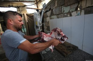 Palestinian in Gaza seen cutting meat to distribute, as part of Eid Al-Adha's Qurbani sacrifice, on 31 July 2020 [Mohammad Asad / Middle East Monitor]