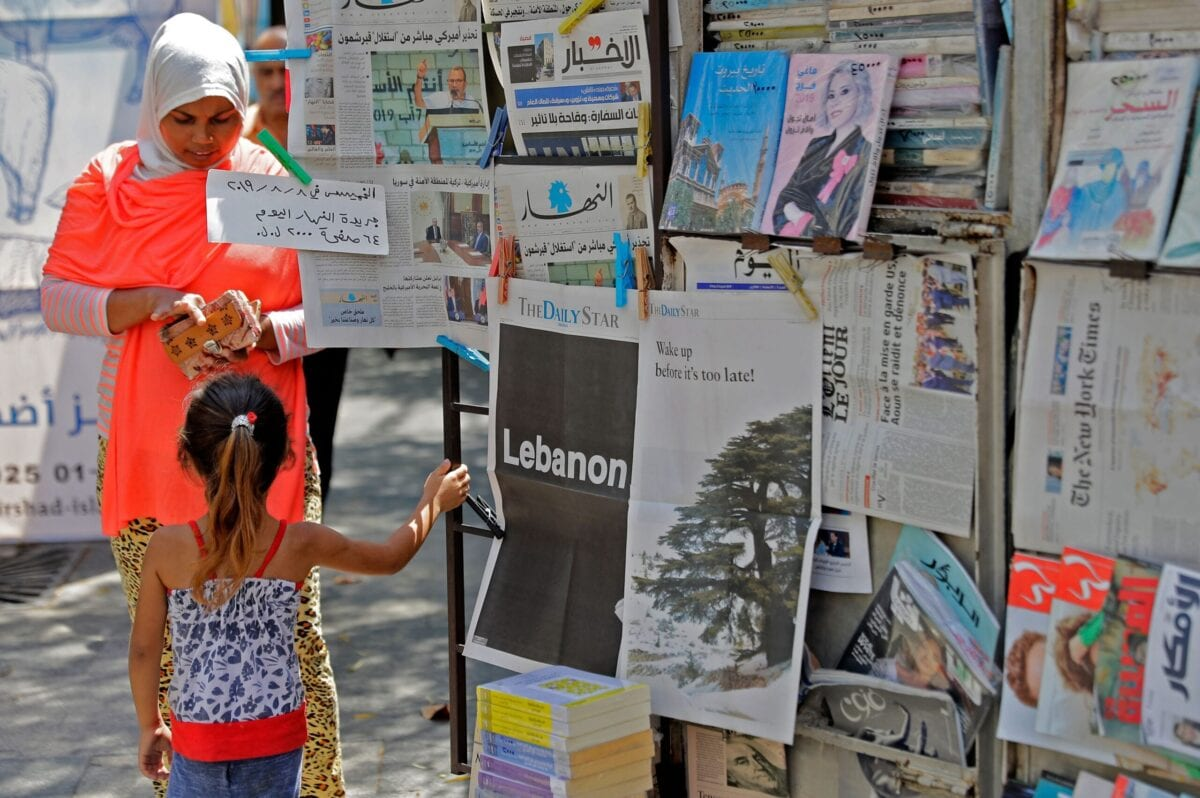 """A girl stands next to a copy of the Lebanese local English-language newspaper """"The Daily Star"""" in the capital Beirut on August 8, 2019[JOSEPH EID/AFP via Getty Images]"""