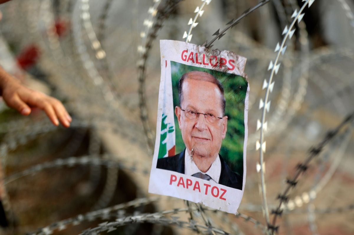 A picture of Lebanese President Michel Aoun hangs on barbed-wire on the road leading to the Presidential Palace in Baabda, on the eastern outskirts of Beirut on 13 November, 2019 [ANWAR AMRO/AFP via Getty Images]