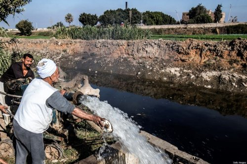 Egyptian farmer Mohamed Omar (C), 65, supplies his farmland with water from a canal, fed by the Nile river, in the village of Baharmis on the outskirts of Egypt's Giza province, northwest of the capital Cairo, on December 1, 2019. [KHALED DESOUKI/AFP via Getty Images]