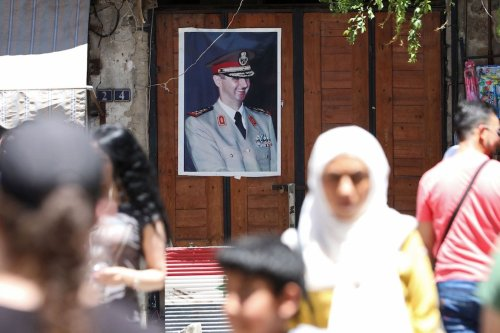 Syrians walk in old Damascus in front of a portrait of Syrian President Bashar al-Assad, on 16 June 2020. [LOUAI BESHARA/AFP via Getty Images]