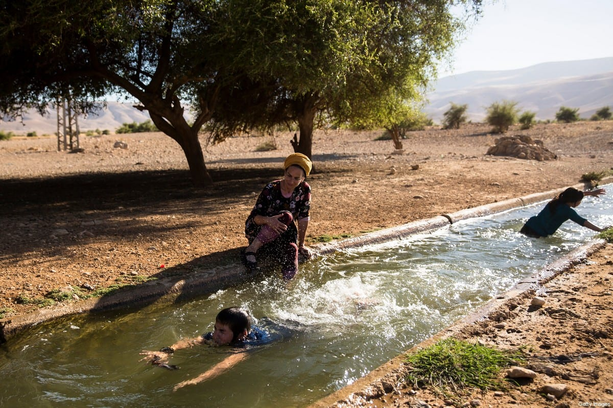 A Jewish settler family swims in the water of the natural spring of Ein Al-AUJA in the occupied Jordan Valley West Bank on 24 June 2020 [Amir Levy/Getty Images]