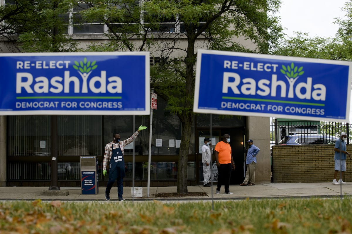Election worker Demario Thurmond, 23, of Detroit, instructs cars where to drop off their ballots outside of the City of Detroit Department of Elections during the Michigan Primary Election on 4 August 2020 in Detroit, Michigan. Among the candidates is U. S Rep. Rashida Tlaib (D-MI) running against fellow Democrat and Detroit City Council President Brenda Jones. [Brittany Greeson/Getty Images]