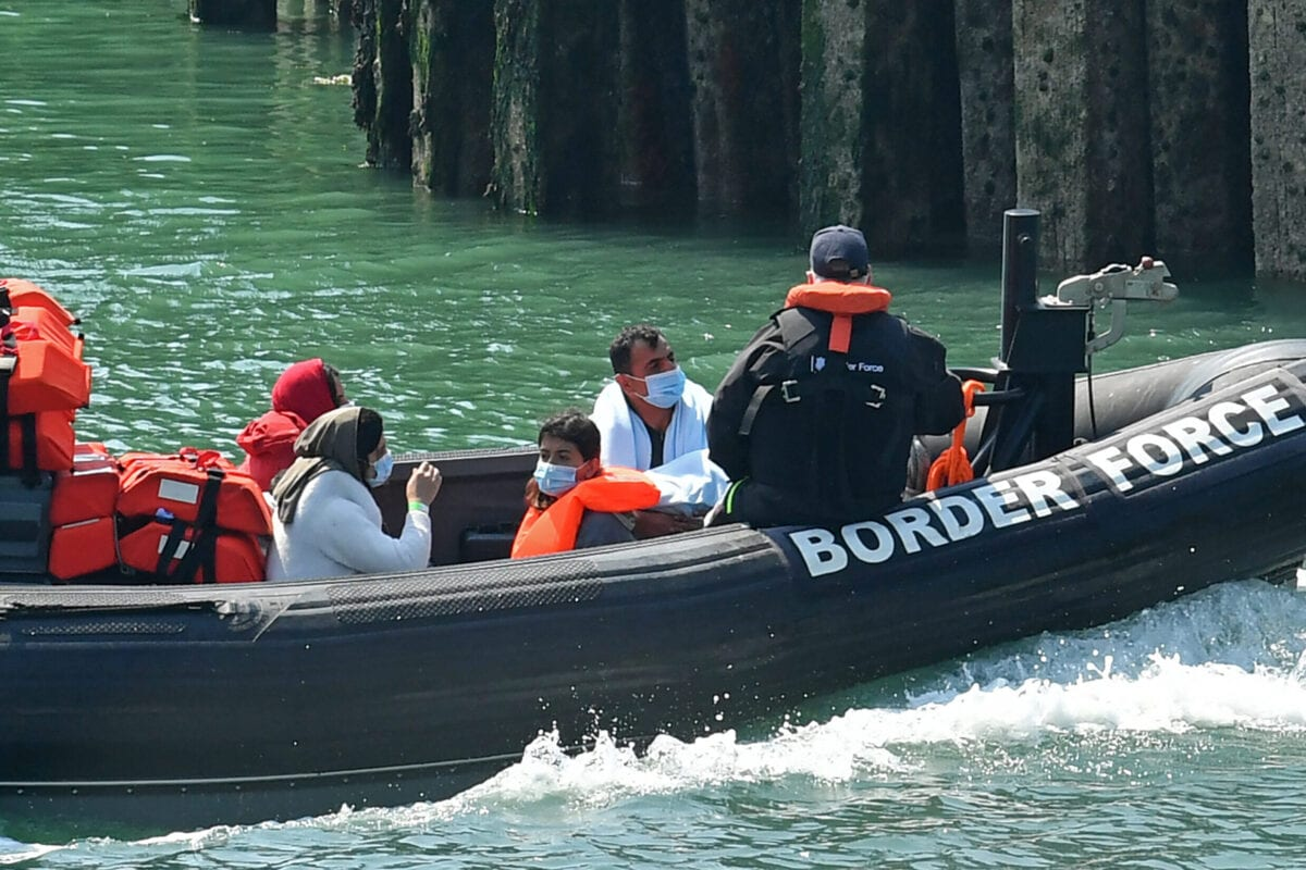 A Border Patrol dinghy brings a group of migrants, believed to have been picked up from boats in the Channel, into harbour at the port of Dover, on the south-east coast of England on August 9, 2020. [GLYN KIRK/AFP via Getty Images]