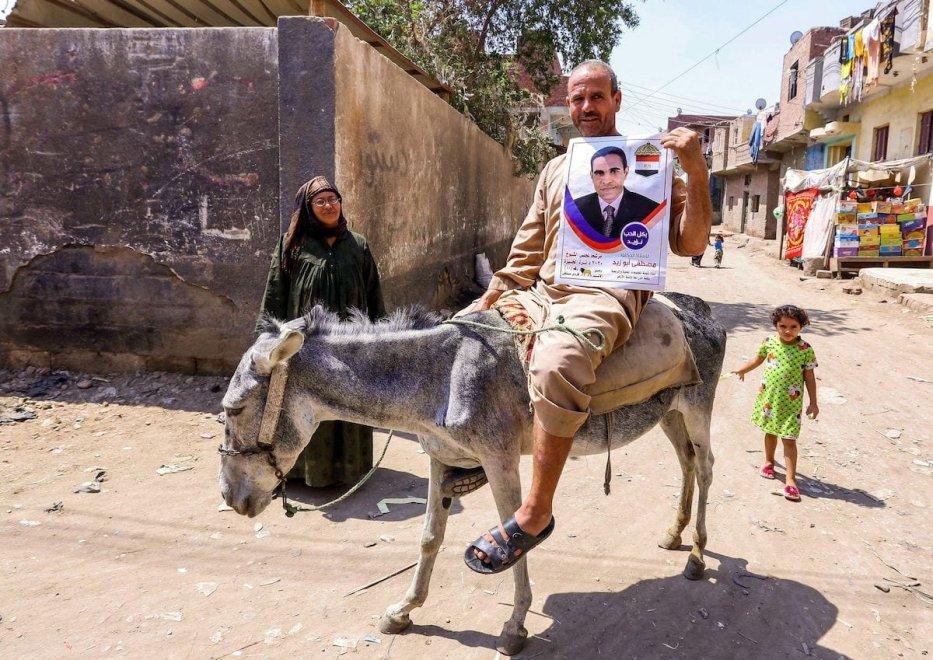 Un hombre montado en un burro cerca de un colegio electoral en la ciudad de el-Ayyat en la provincia de Giza al sur de la capital egipcia el 11 de agosto de 2020 sostiene un cartel electoral para un candidato que se postula para las elecciones de la cámara alta en el Senado recién creado. [AFP via Getty Images]