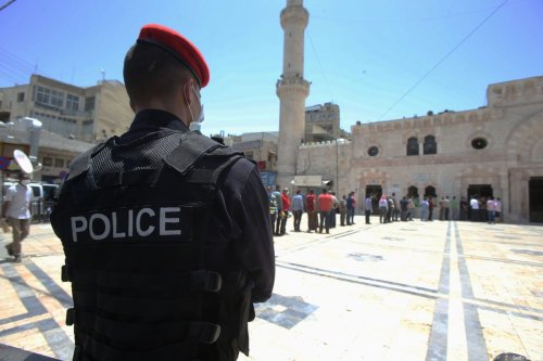 A Jordanian policeman watches a queue of men as they attend the Friday prayers under restricted health measures in Al Husseini mosque in the downtown on 5 June 2020 in Amman, Jordan. [Jordan Pix/Getty Images]