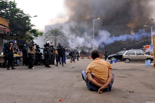 A handcuffed protester sits on the ground as Egyptian security forces move in to disperse supporters of Egypt's ousted president Mohamed Morsi by force in a huge camp in Cairo's Al-Nahda square on August 14, 2013. The operation began shortly after dawn when security forces surrounded the sprawling Rabaa al-Adawiya camp in east Cairo and a similar one at Al-Nahda square, in the centre of the capital, launching a long-threatened crackdown that left dozens dead. AFP PHOTO / ENGY IMAD (Photo credit should read Engy Imad/AFP via Getty Images)