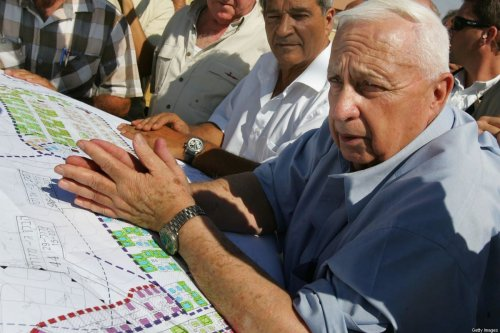 Then Israeli Prime Minister Ariel Sharon leans over housing plans as he meets with contractors who are building temporary housing for settlers due to be evacuated from the Gaza Strip under his disengagement plan July 5, 2005 at the Nitzanim construction site in southern Israel [David Silverman/Getty Images]