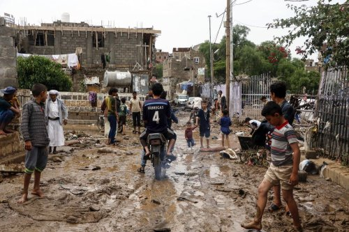 People are seen amid muds on damaged streets hit by a flood due to heavy rain in Sanaa, Yemen on 7 August 2020 [Mohammed Hamoud/Anadolu Agency]