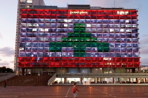 The city hall in the Israeli coastal city of Tel Aviv is lit up in the colours of the Lebanese national flag in solidarity, on August 5, 2020 [JACK GUEZ/AFP via Getty Images]