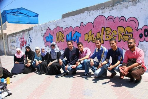 "Palestinian youth posing in front of a graffiti ""We Are Not Numbers"" [Twitter]"