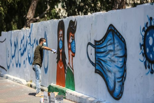 Palestinian artist paints graffitis to raise the awareness of public on coronavirus (Covid-19) pandemic in Deyr al Balah, Gaza on September 13, 2020 [Ali Jadallah - Anadolu Agency]