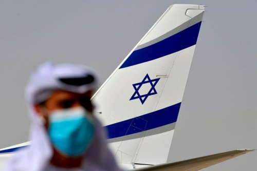 An Emirati official stands near an air-plane of El Al following the first-ever commercial flight from Israel to the UAE, on 31 August 2020 [KARIM SAHIB/AFP/Getty Images]