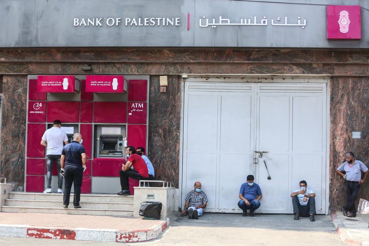 Palestinians wearing protective masks maintain social distancing while waiting in ATM line during the coronavirus (COVID-19) pandemic in Gaza City, Gaza on 1 September 2020. [Ali Jadallah - Anadolu Agency]