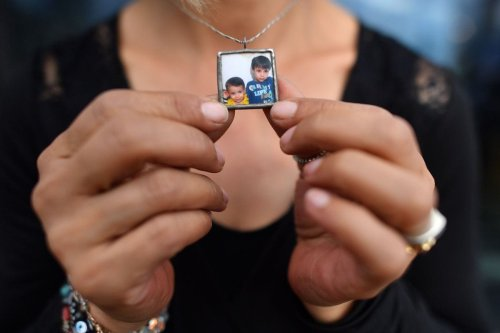 Tima Kurdi, co-founder of the The Kurdi Foundation, holds her necklace bearing an image of her nephews, Alan and Ghalib Kurdi, as she poses for a photograph in London on 15 August 2018. [BEN STANSALL/AFP via Getty Images]