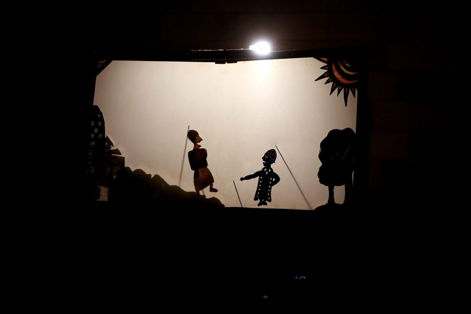 Spectators watch Egypt's Aragoz shadow puppets show in Beit al-Sehemi, in Cairo's Gamaliya district, on November 15, 2019 [MOHAMED EL-SHAHED/AFP via Getty Images]