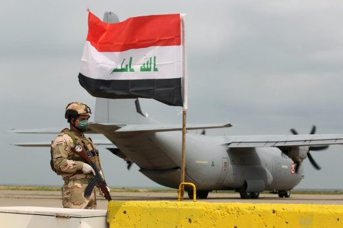 An Iraqi soldiers stands guard in front US military air carrier at the Qayyarah air base, where US-led troops in 2017 had helped Iraqis plan out the fight against Daesh in nearby Mosul in northern Iraq, before a planned US pullout on 26 March 2020. [AHMAD AL-RUBAYE/AFP via Getty Images]