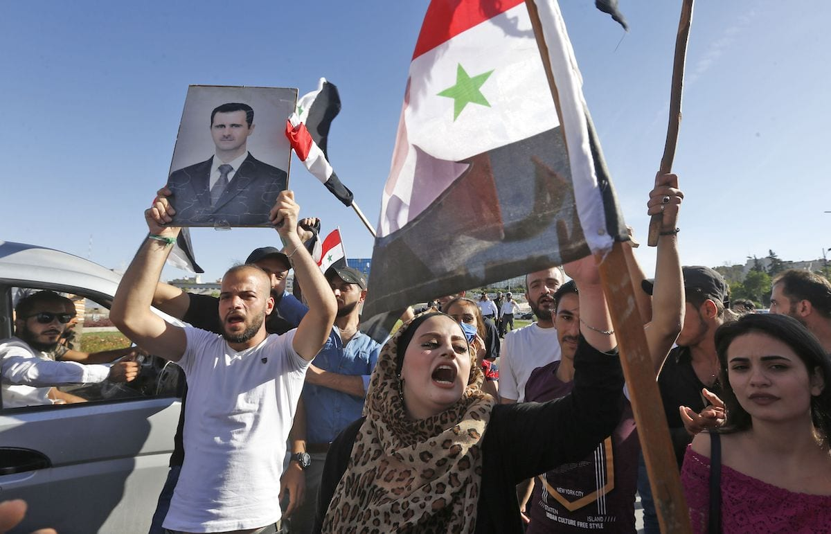 People chant slogans as they wave Syrian national flags and pictures of President Bashar al-Assad during a demonstration in support of Assad and against US sanctions on the country, at the Umayyad Square in the centre of the capital Damascus on 11 June 2020. [LOUAI BESHARA/AFP via Getty Images]