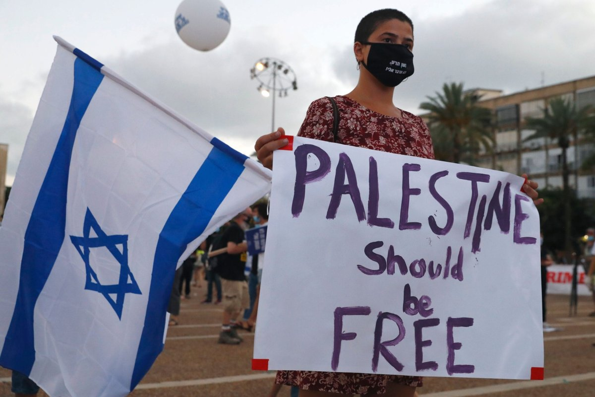 A protester, wearing a protective mask due to the COVID-19 pandemic, holds placards during a demonstration in Tel Aviv's Rabin Square to denounce Israel's plan to annex parts of the occupied West Bank, on 23 June 2020. [JACK GUEZ/AFP via Getty Images]