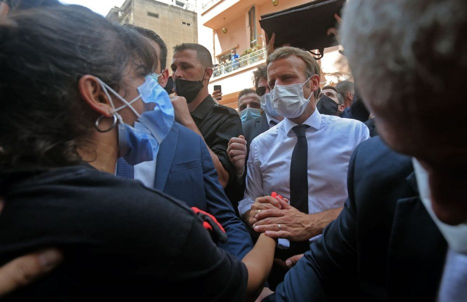 French President Emmanuel Macron comforts a Lebanese youth during a visit to the Gemmayzeh neighbourhood, which has suffered extensive damage due to a massive explosion in the Lebanese capital, on 6 August 2020. [AFP via Getty Images]