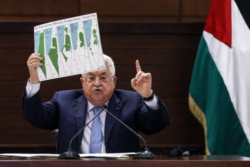 Palestinian president Mahmud Abbas holds a placard showing maps of historical Palestine [ALAA BADARNEH/POOL/AFP via Getty Images]