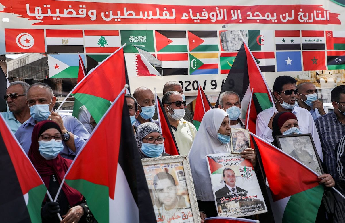 "Demonstrators protest with Palestinian flags as they stand before a banner showing the flags of Arab League member states with text in Arabic above reading ""history will glorify but those faithful to Palestine and its cause"", during a protest against the UAE and Bahrain's decisions to normalise relations with Israel, in Nablus in the occupied West Bank on 15 September 2020. [JAAFAR ASHTIYEH/AFP via Getty Images]"