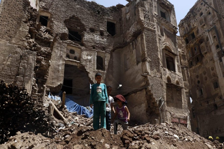 Children stand on the rubble of a historic building after it collapsed partially due to the heavy rains in the Old City of Sanaa, on August 13, 2020 in Sana'a, Yemen [Mohammed Hamoud / Getty Images]