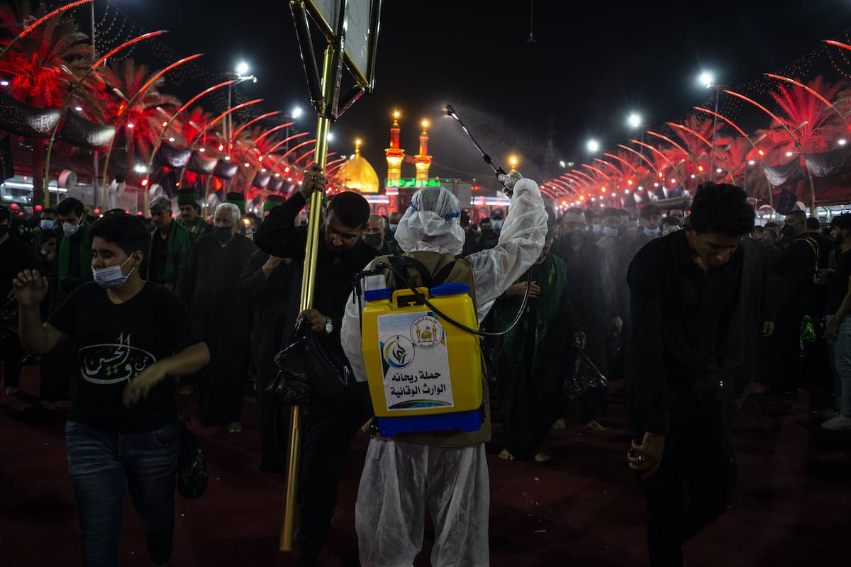 A man sprays disinfectant over people taking part in mourning rituals to commemorate Ashura during the Islamic month of Muharramon on August 29, 2020 in Karbala, Iraq [Hawre Khalid/Getty Images]