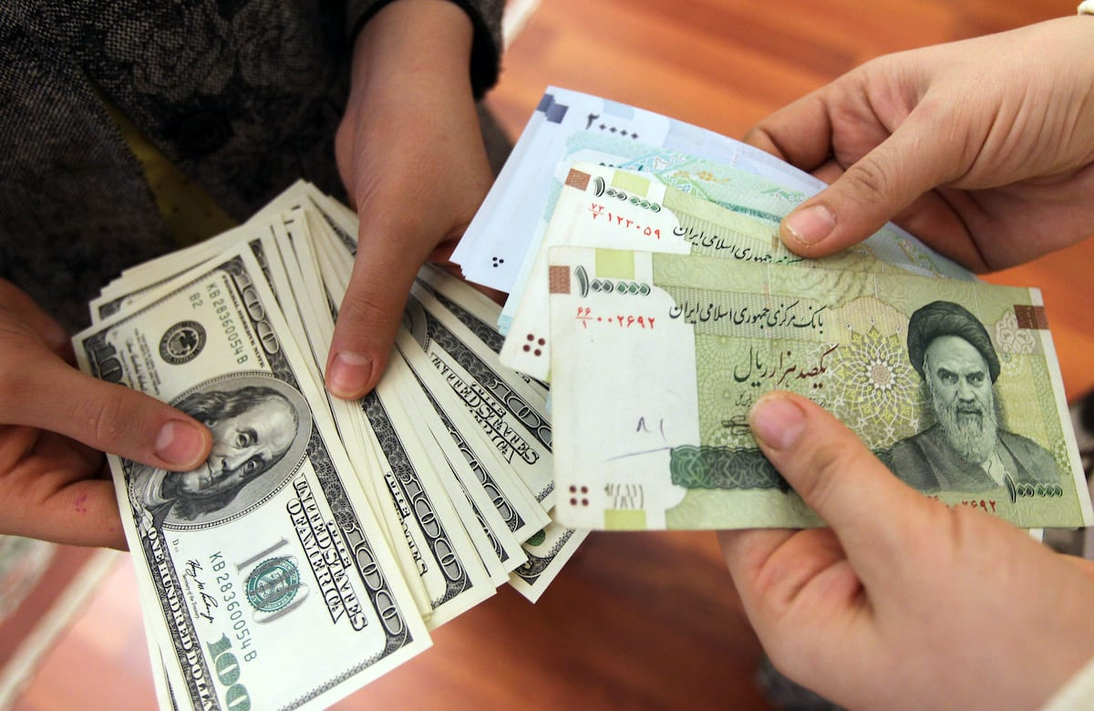 Iranians counting and exchanging the United States 100-dollar bills and Iran's Rial banknotes, on 12 January 2012 [ATTA KENARE/AFP via Getty Images]