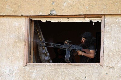 A member of the self-styled Libyan National Army, loyal to the country's east strongman Khalifa Haftar, fires a machine gun during clashes with militants in Benghazi's central Akhribish district on 19 July 2017. [ABDULLAH DOMA/AFP via Getty Images]