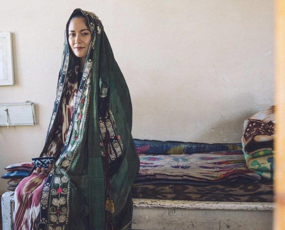 The Paranja'- Subhi Bora, wearing a traditional Central Asian robe and holding an Uyghur Doppa. (Captured by Nadir Nahdi)
