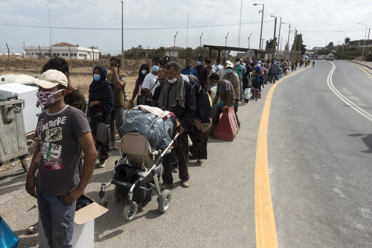 LESBOS, GREECE - SEPTEMBER 26: Refugees wait in a queue at the entrance of a temporary camp as they and their belongings are checked by police officers before settling in after the Moria refugee camp became unuseable following fires that erupted on September 9, in the Greek island of Lesbos, on September 26, 2020. ( Ayhan Mehmet - Anadolu Agency )