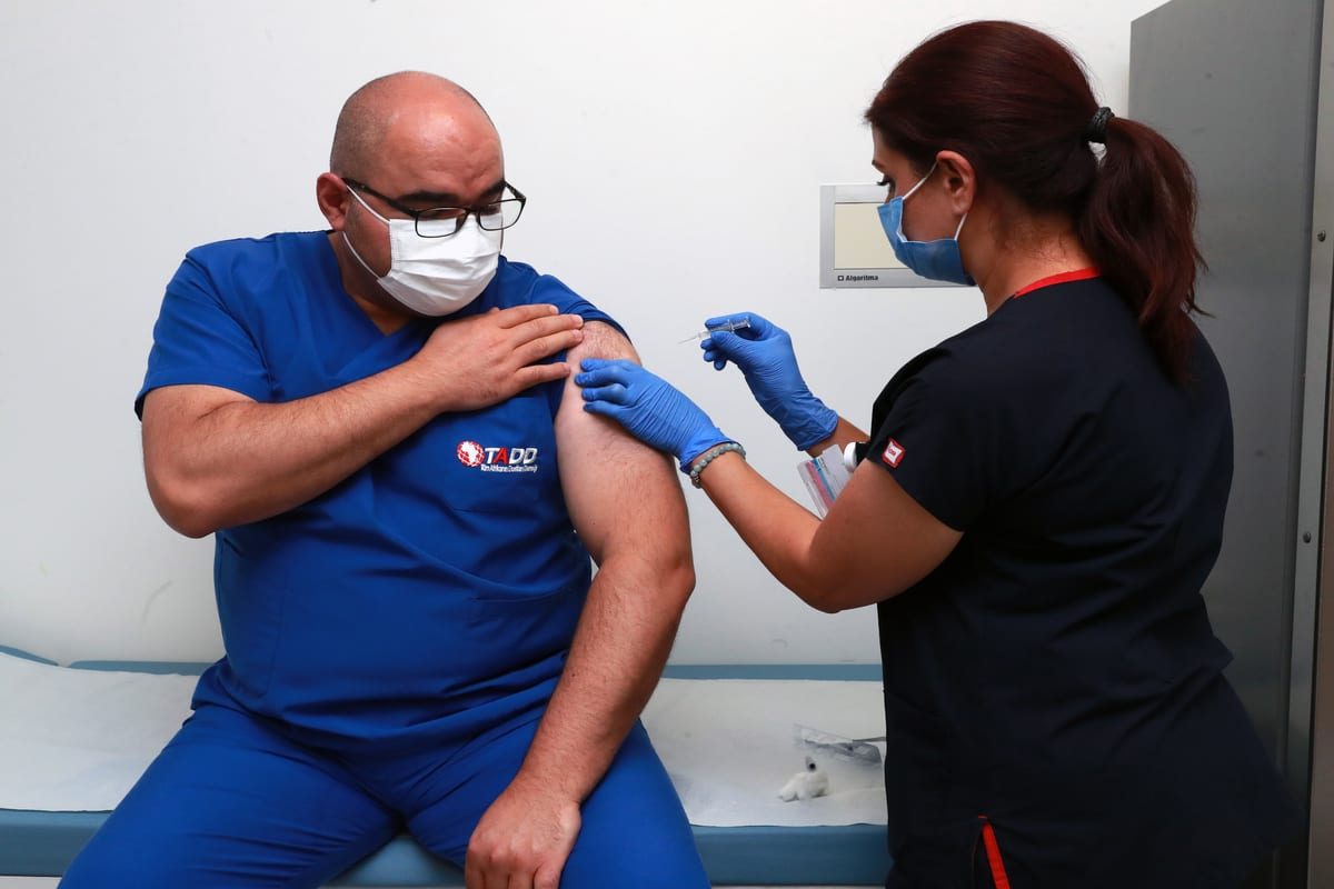 Volunteer Aziz Ahmet Surel (L), head coordinator doctor of Ankara City Hospital receives a Chinese Sinovac vaccine shot for (coronavirus) COVID-19 on 6 October 2020 in Ankara, Turkey. [Ministry of Health of Turkey - Anadolu Agency]