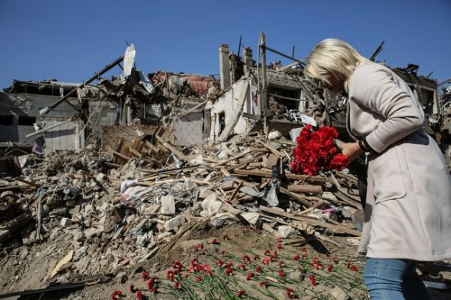 A woman lays a carnation for children on wreckage of a house for children who killed and injured in the attack after Armenian army's alleged attacks with long-range missiles, in Ganja city of Azerbaijan on October 12, 2020 [Onur Çoban - Anadolu Agency]