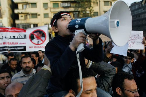 An Egyptian boy wields a megaphone as he chants anti-government slogans in Tahrir Square the afternoon of 31 January 2011 in central Cairo, Egypt. [Chris Hondros/Getty Images]