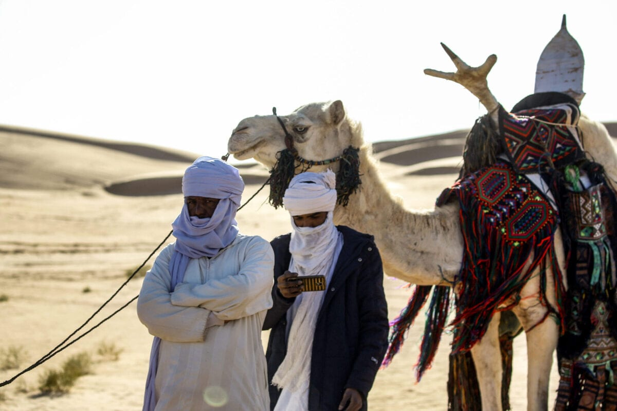 A Tuareg tribesman uses his cell phone to film while attending a traditional ceremony in the Libyan desert in the western Awal region near the borders with Tunisia and Algeria, about 600 kilometres southwest of the capital Tripoli, on March 29, 2019. - The Tuaregs were forced to leave their town of Ghadames, in Libya's far west, after being accused of fighting alongside longtime ruler Moamer Kadhafi's forces in 2011. They found refuge in the Awal region in the desert about 50 kilometres north of Ghadames. (Photo by Imed LAMLOUM / AFP) (Photo credit should read IMED LAMLOUM/AFP via Getty Images)