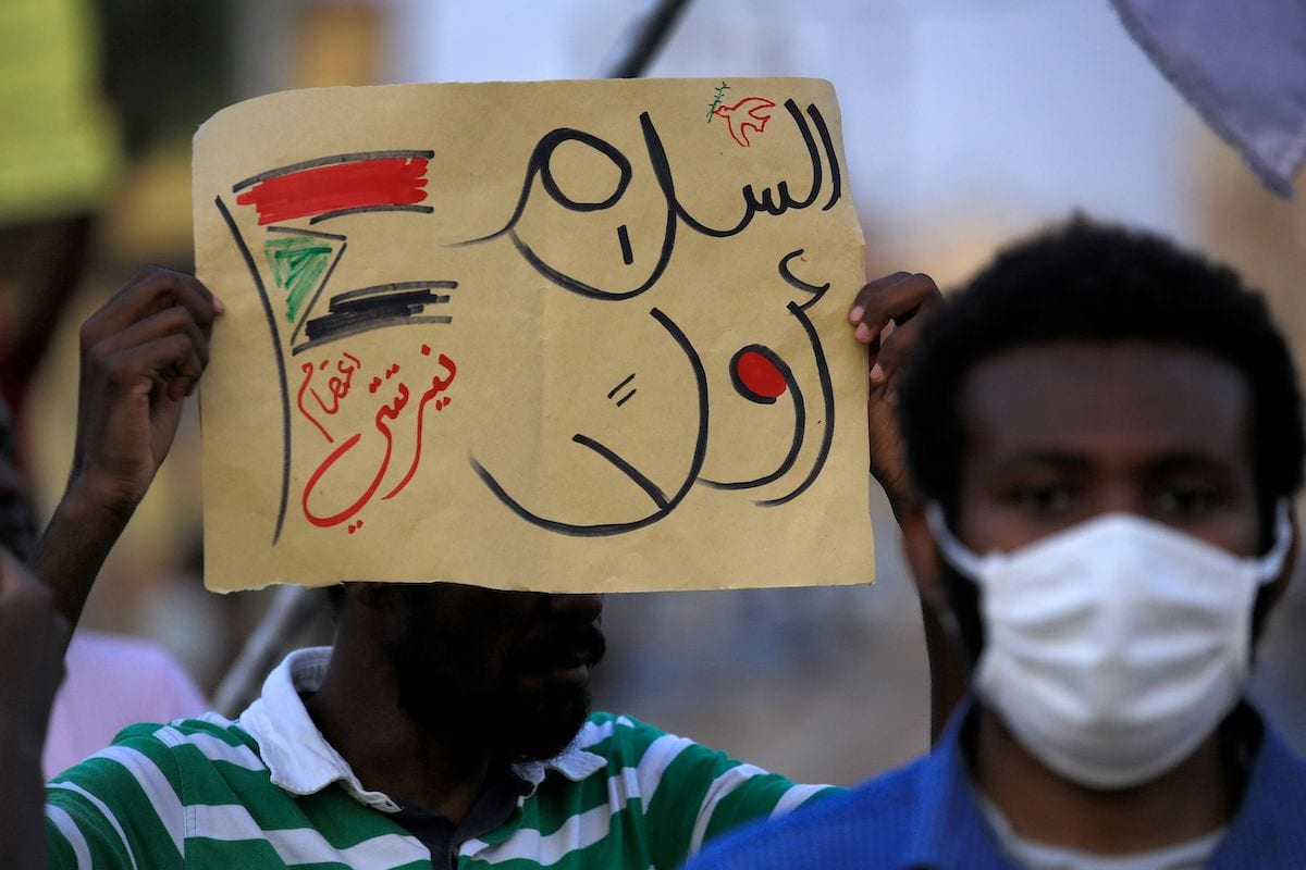 """A demonstrator holds up a sign reading in Arabic """"peace first, Nertiti sit-in"""" along with a drawn Sudanese flag, during a protest outside the Sudanese Professionals Association in the Garden City district of Sudan's capital Khartoum on 4 July 2020, in solidarity with the people of the Nertiti region of Central Darfur province in the country's southwest. [ASHRAF SHAZLY/AFP via Getty Images]"""
